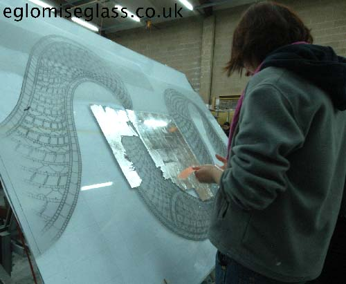 applying silver leaf on the back of the glass sheet